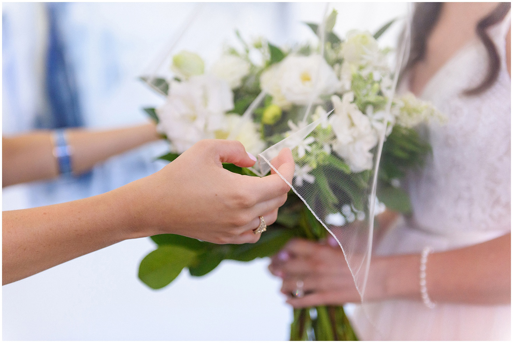 A bridesmaid helps adjust the bride's veil for a Butterfield Country Club wedding.
