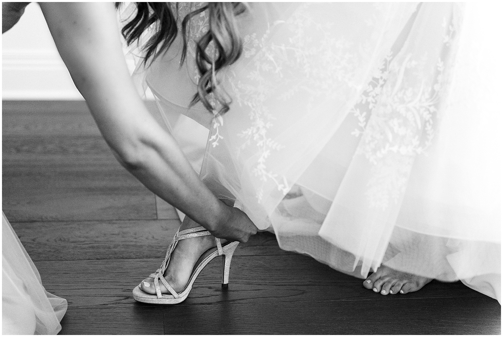 A bridesmaid helps a bride into her shoes for a Butterfield Country Club wedding.