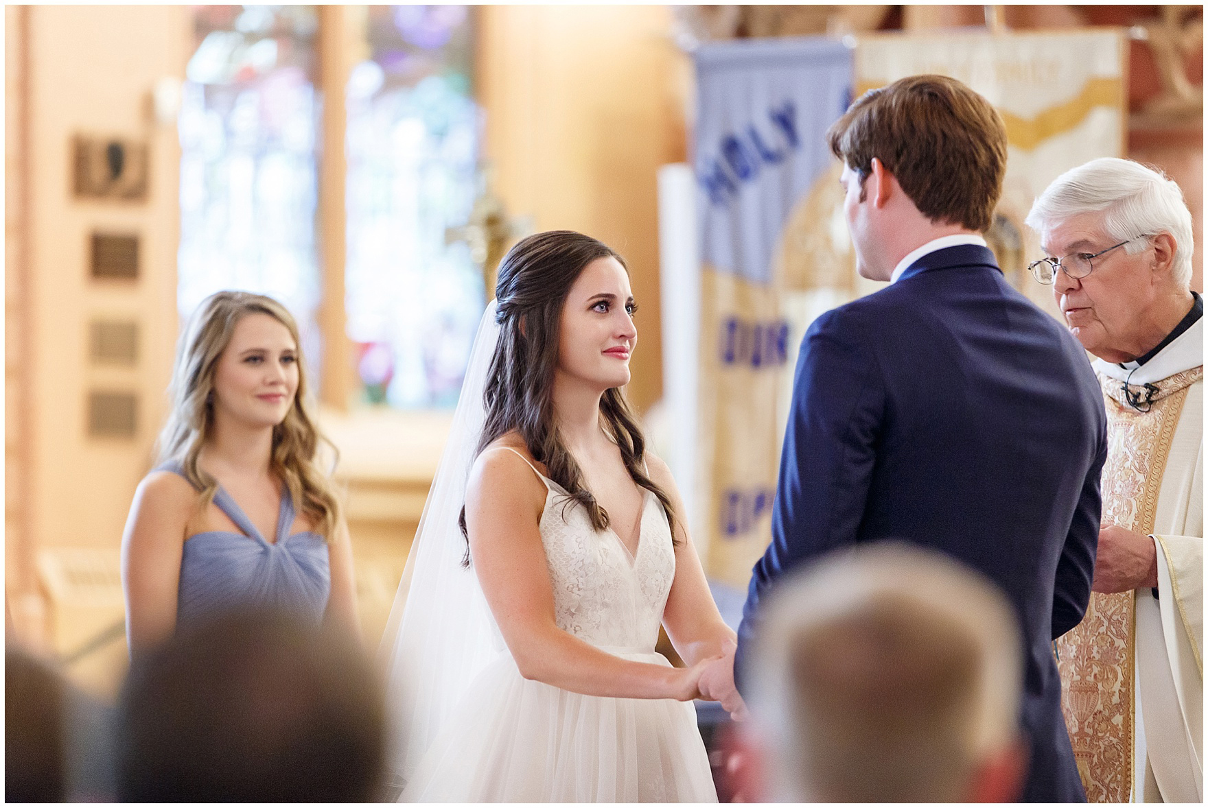 The bride and groom exchange vows in Chicago's historic Holy Family Church, site of the ceremony for a Butterfield Country Club wedding.