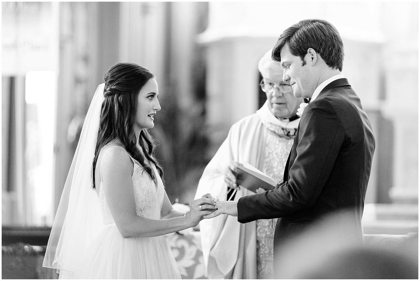 The bride and groom exchange rings in Chicago's historic Holy Family Church, site of the ceremony for a Butterfield Country Club wedding.
