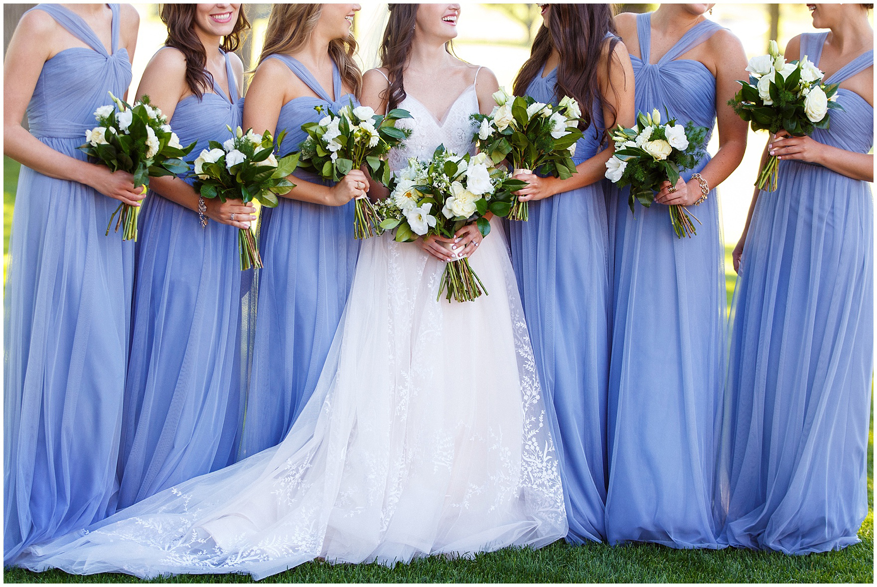 Bridesmaids in pale blue stand with the bride, holding bouquets by Flowers for Dreams, during a Butterfield Country Club wedding.