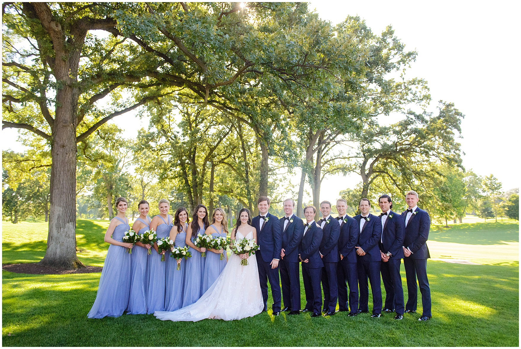 The bridal party poses on a gorgeous summer evening during a Butterfield Country Club wedding.