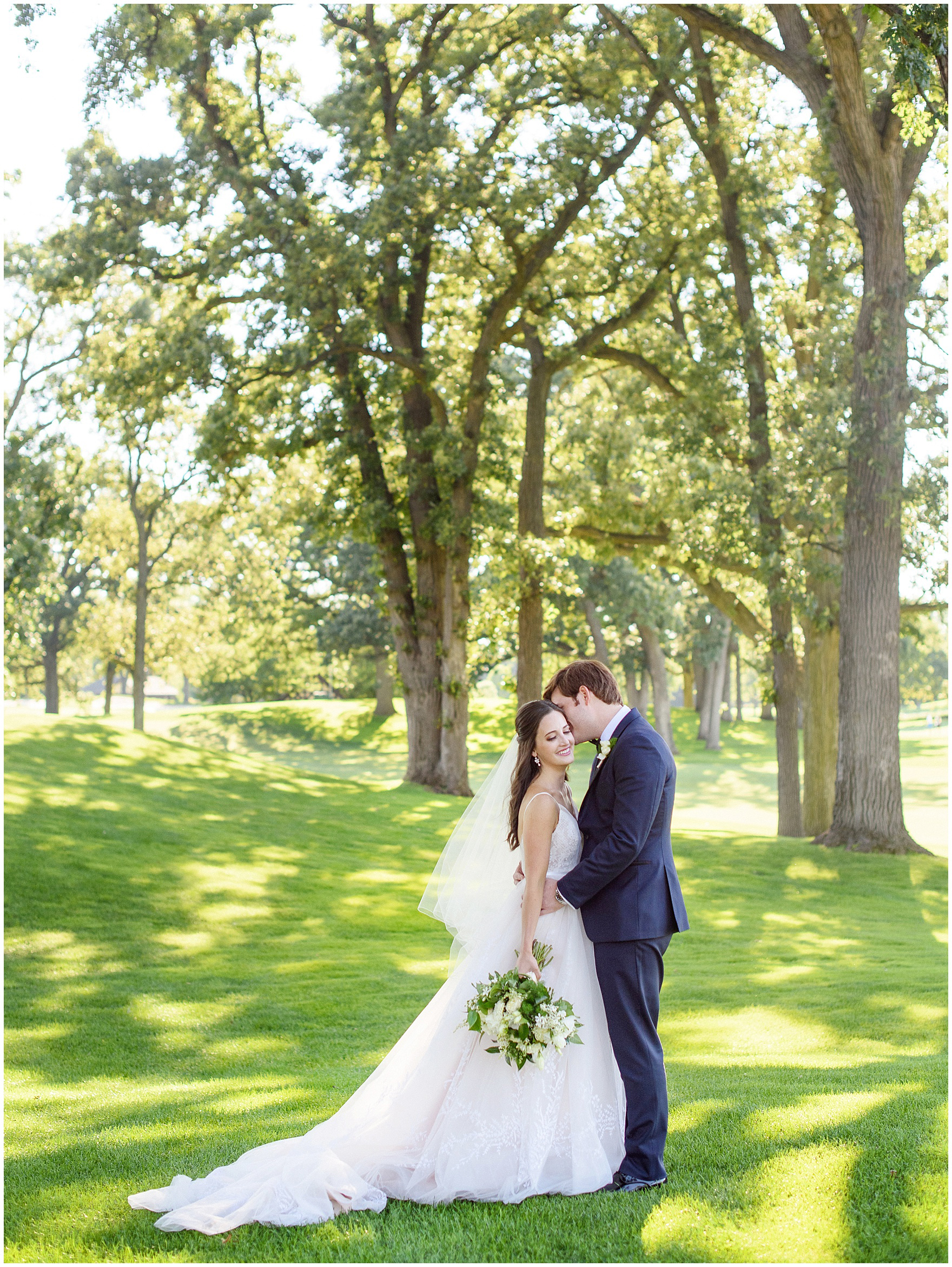 The bride and groom smile for portraits during a Butterfield Country Club wedding.