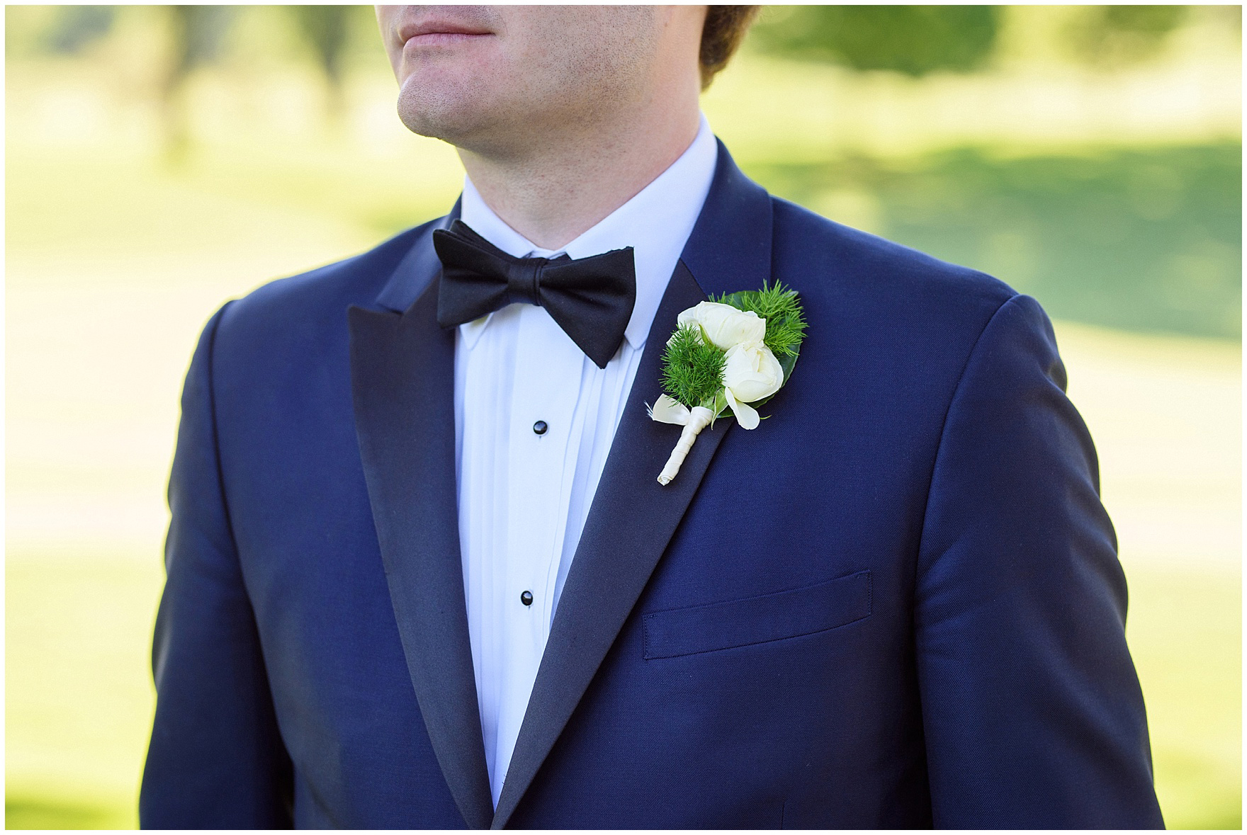 Photograph of a groom in a navy tuxedo with a boutonniere by Flowers for Dreams during a Butterfield Country Club wedding.