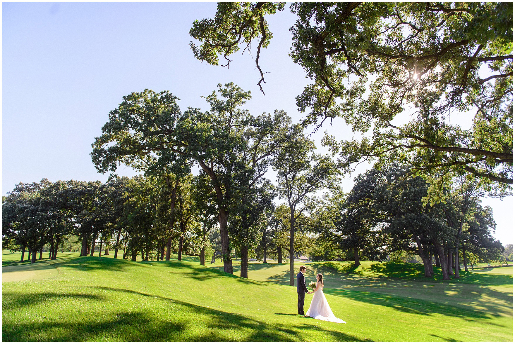 The bride and groom stand hand in hand on the golf course during a Butterfield Country Club wedding.