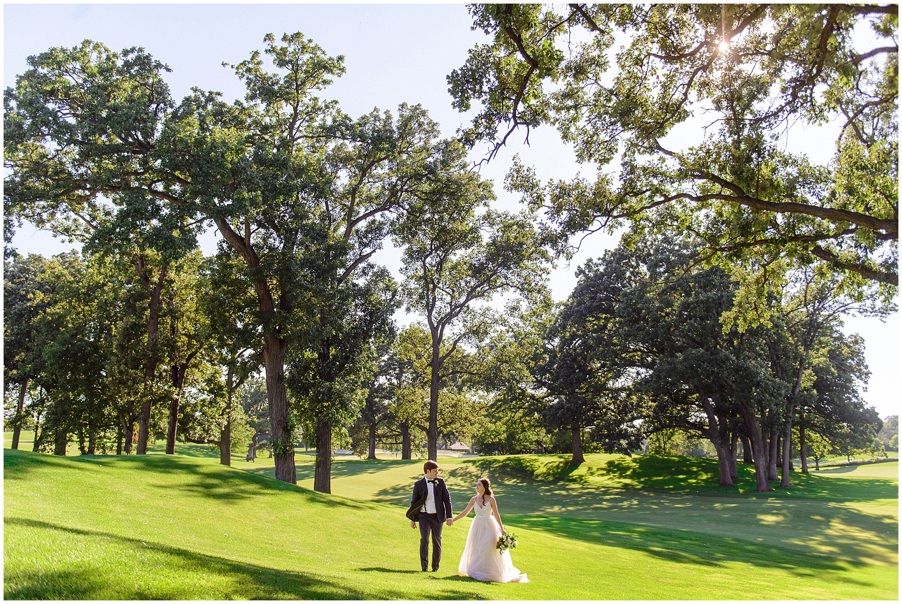 The bride and groom walk and laugh during a Butterfield Country Club wedding.
