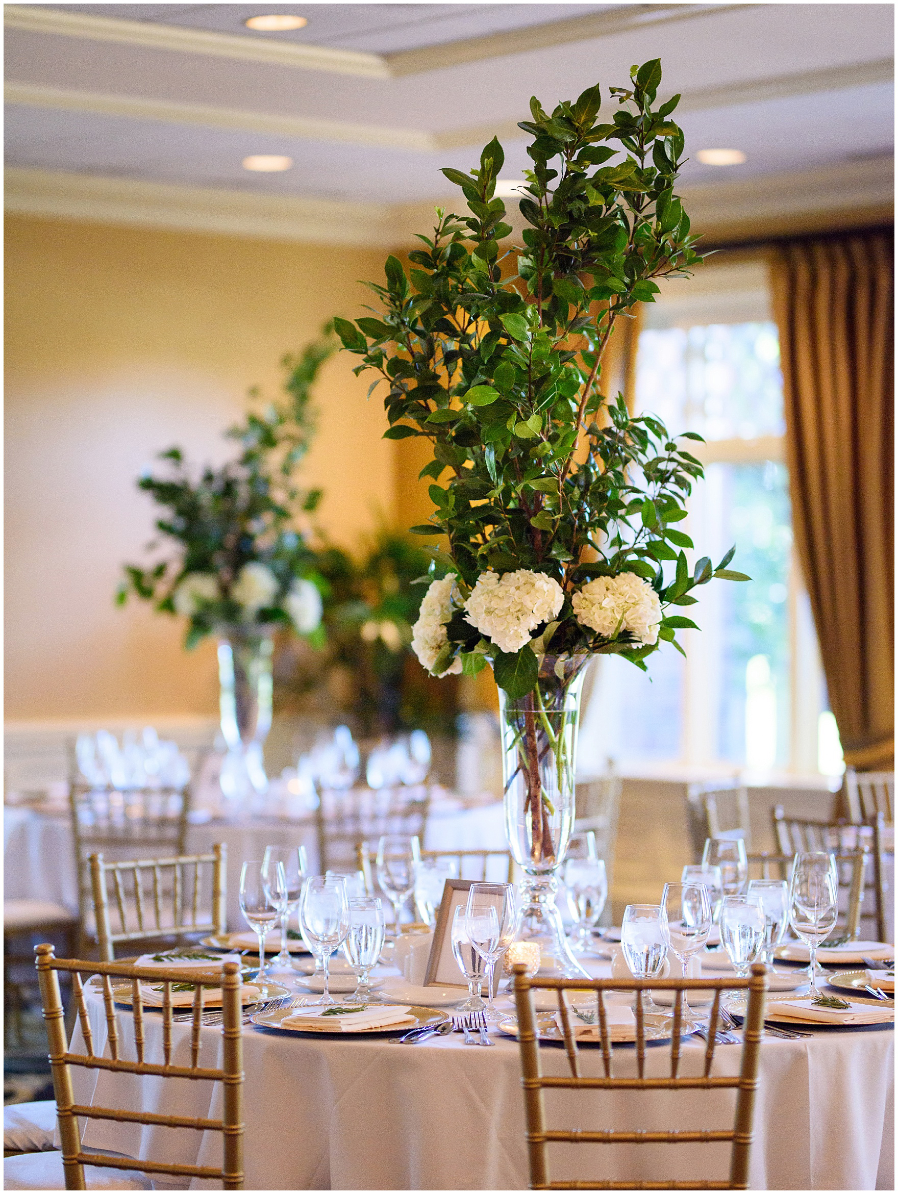 The ballroom is set for dinner with florals by Flowers for Dreams during a Butterfield Country Club wedding.