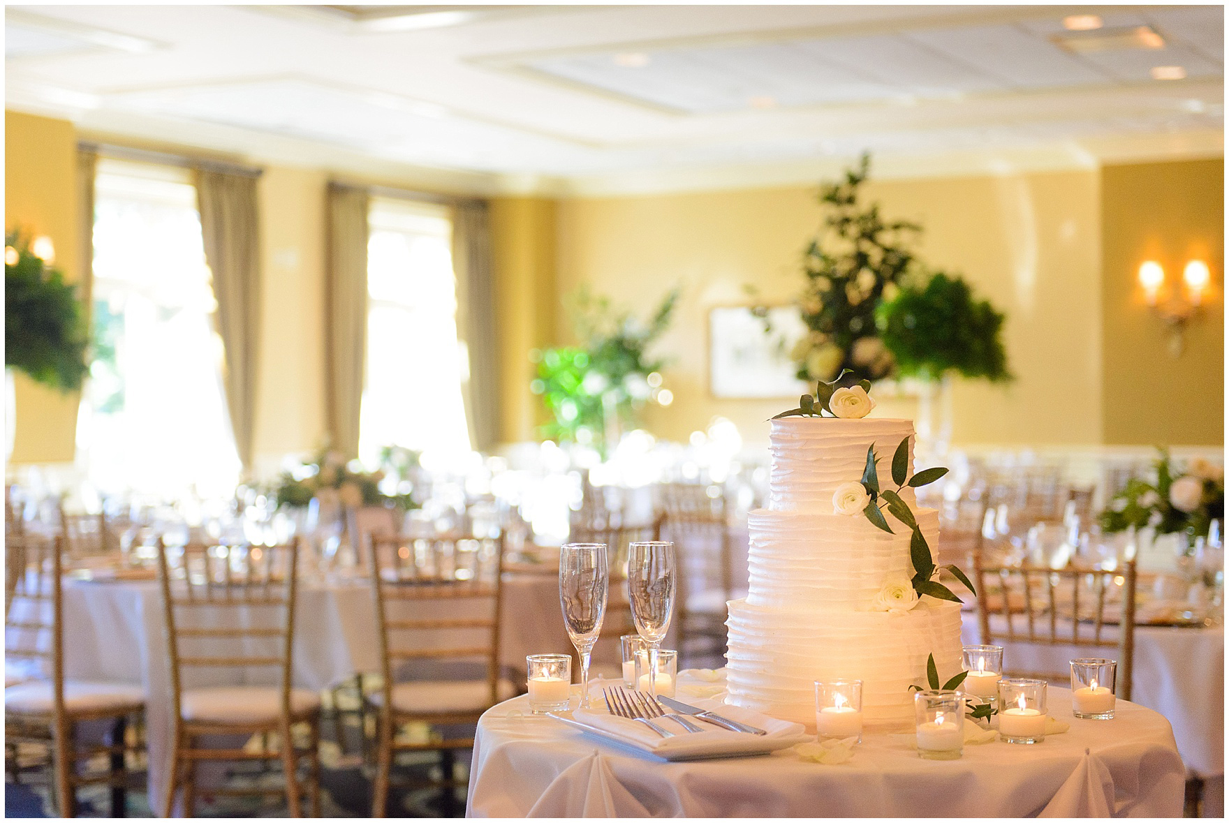 A cake by Toni Patisserie is displayed during a Butterfield Country Club wedding.