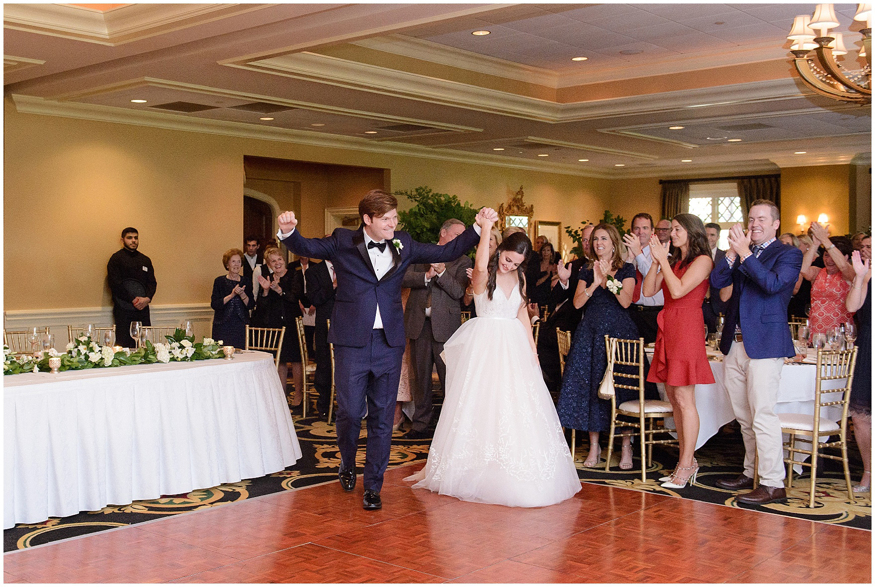 The bride and groom enter their reception to cheers during a Butterfield Country Club wedding.