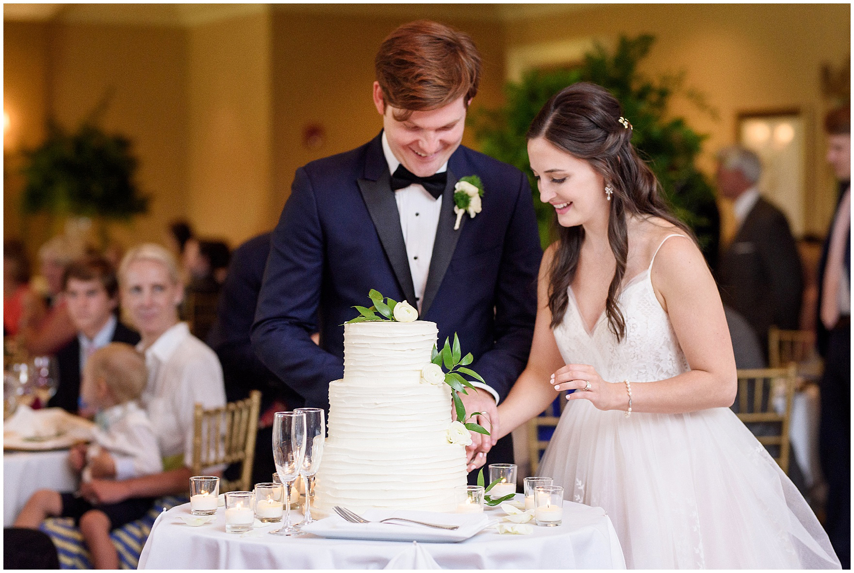 The bride and groom cut their cake by Toni Patisserie during a Butterfield Country Club wedding.