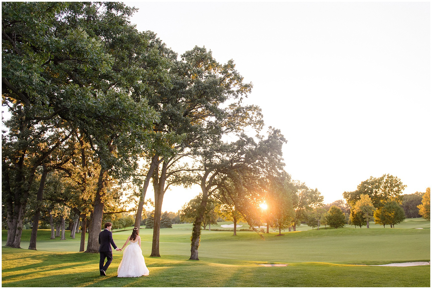 The bride and groom walk and embrace at sunset at their Butterfield Country Club wedding.