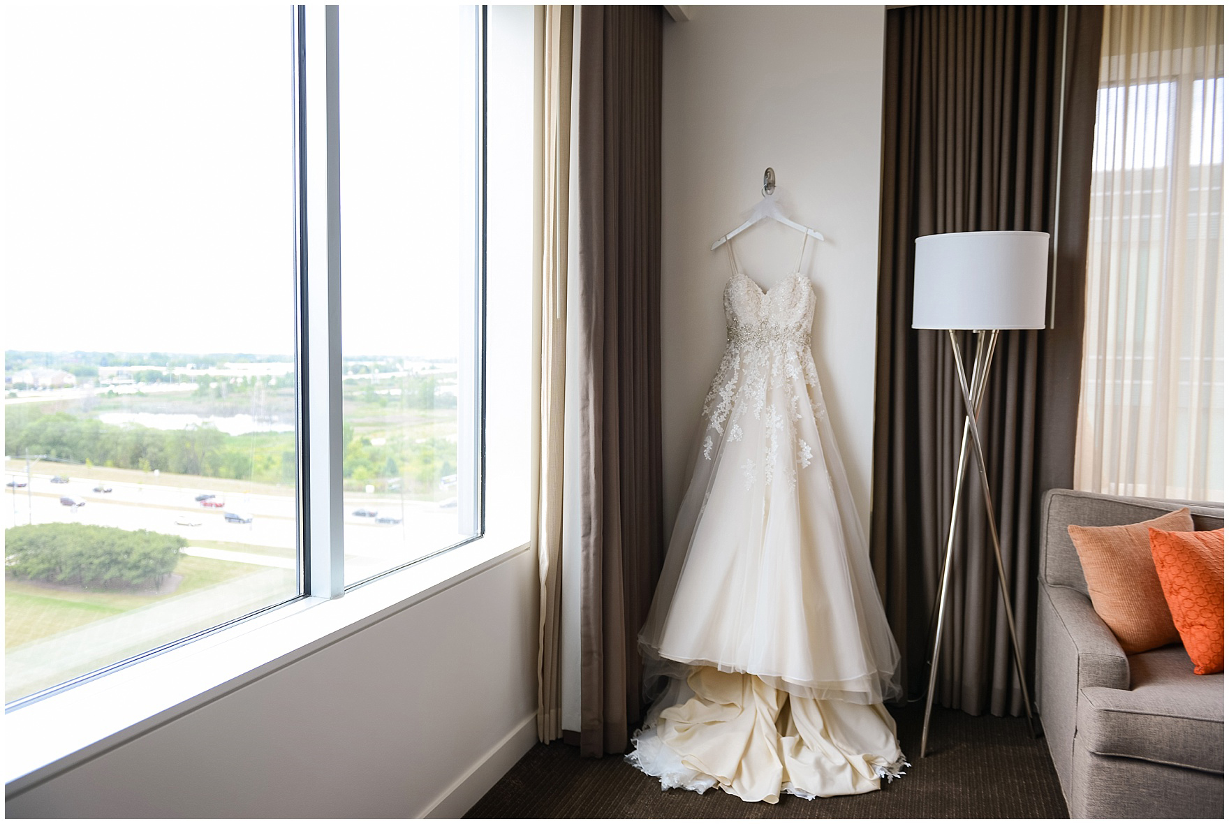 The bride's dress hangs in her hotel suite for a Hotel Arista Naperville wedding.