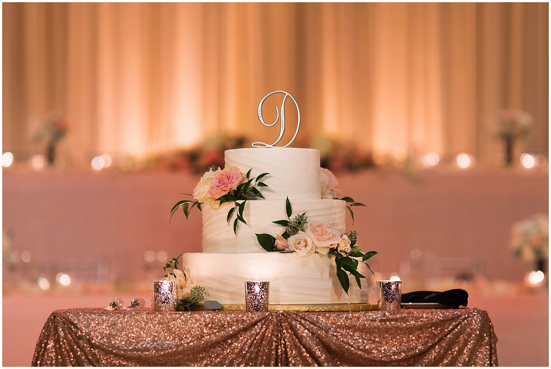 A three tiered wedding cake is the centerpiece for an elegant rose and gold candlelit reception for a Hotel Arista Naperville wedding.