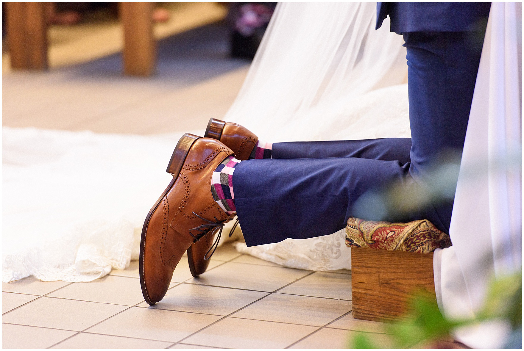 The groom kneels during the ceremony for a St. Josephs Downers Grove Pinstripes Oak Brook, Illinois wedding.