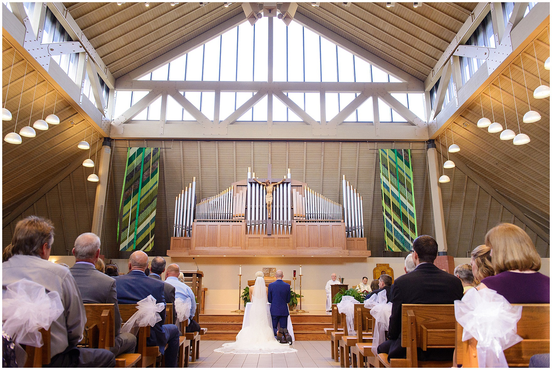 The bride and groom kneel during the ceremony for a St. Josephs Downers Grove Pinstripes Oak Brook, Illinois wedding.