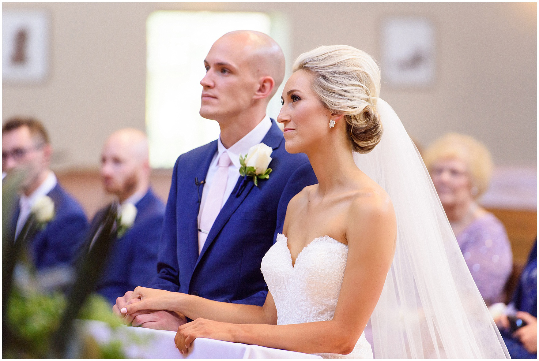 The bride and groom hold hands during the ceremony for a St. Josephs Downers Grove Pinstripes Oak Brook, Illinois wedding.