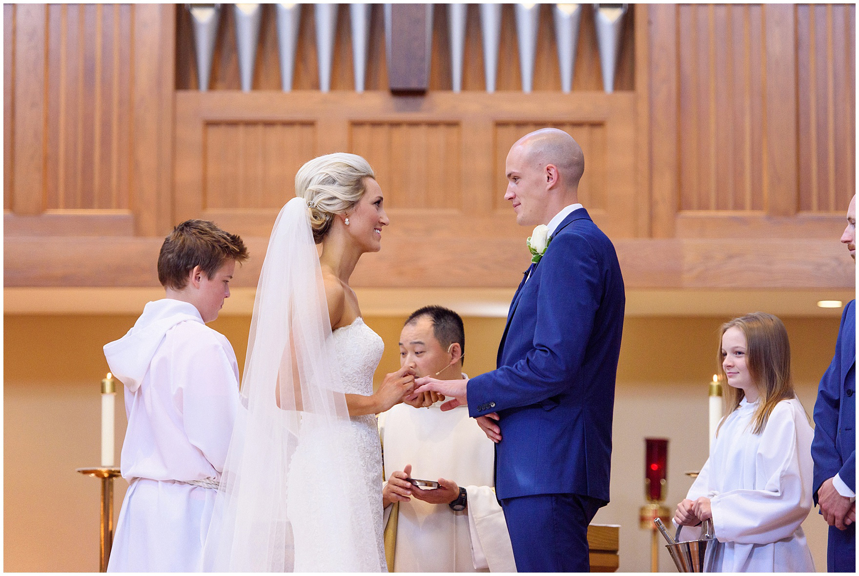 The bride and groom exchange rings during the ceremony for a St. Josephs Downers Grove Pinstripes Oak Brook, Illinois wedding.