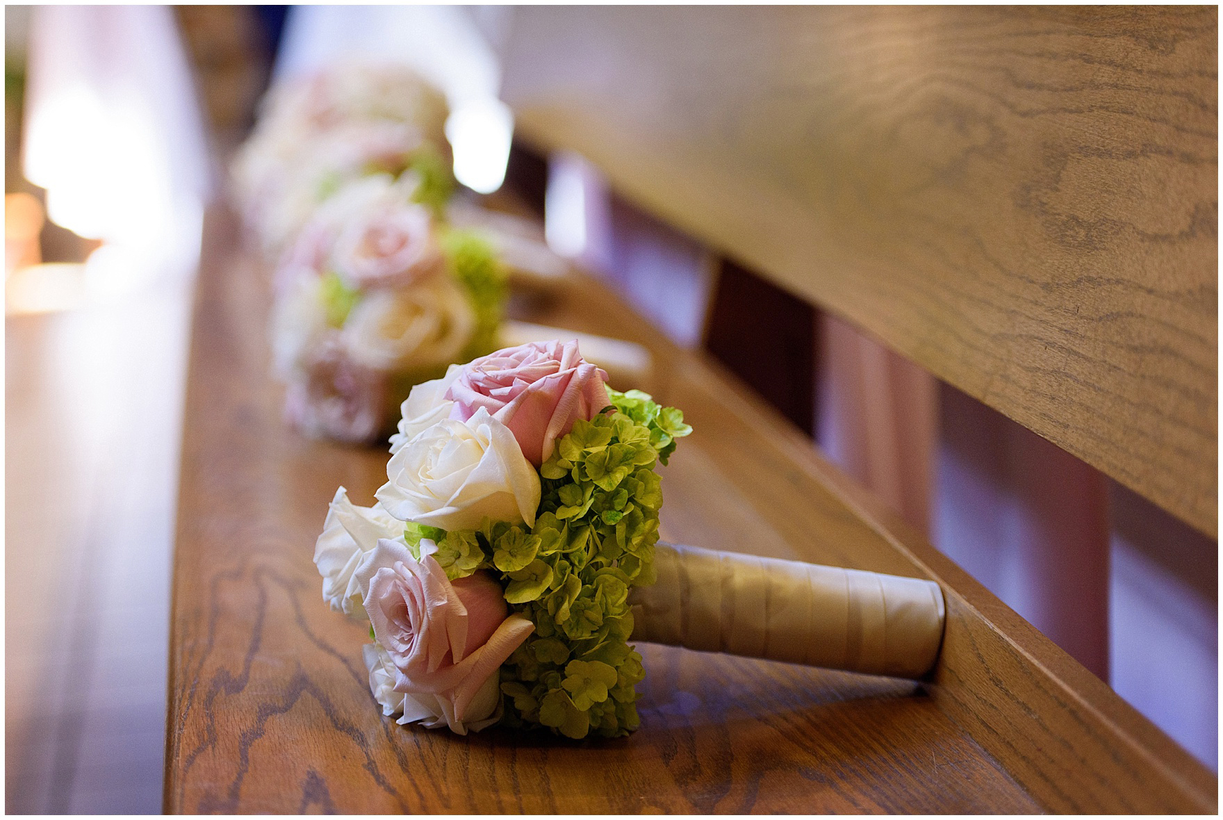 Bouquets of roses on the pew during the ceremony for a St. Josephs Downers Grove Pinstripes Oak Brook, Illinois wedding.