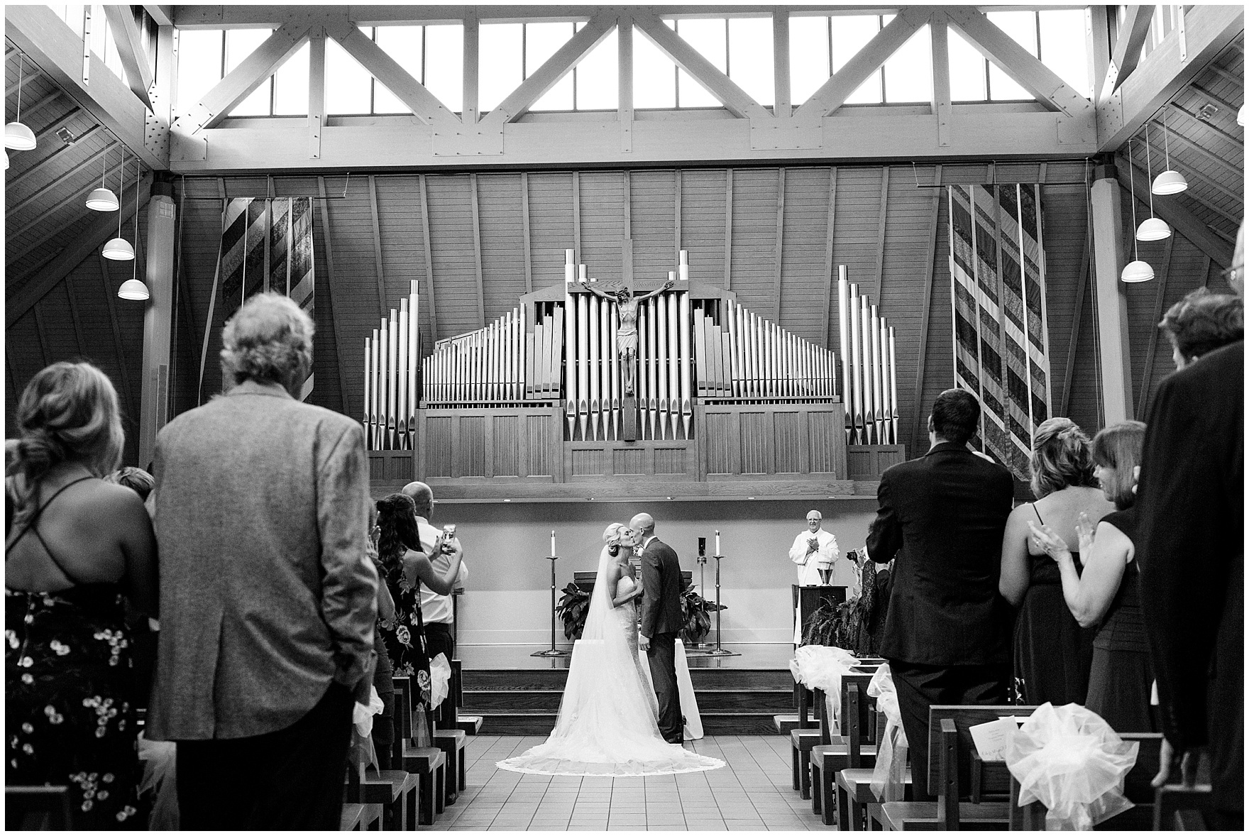 A bride and groom kiss during the ceremony for a St. Josephs Downers Grove Pinstripes Oak Brook, Illinois wedding.