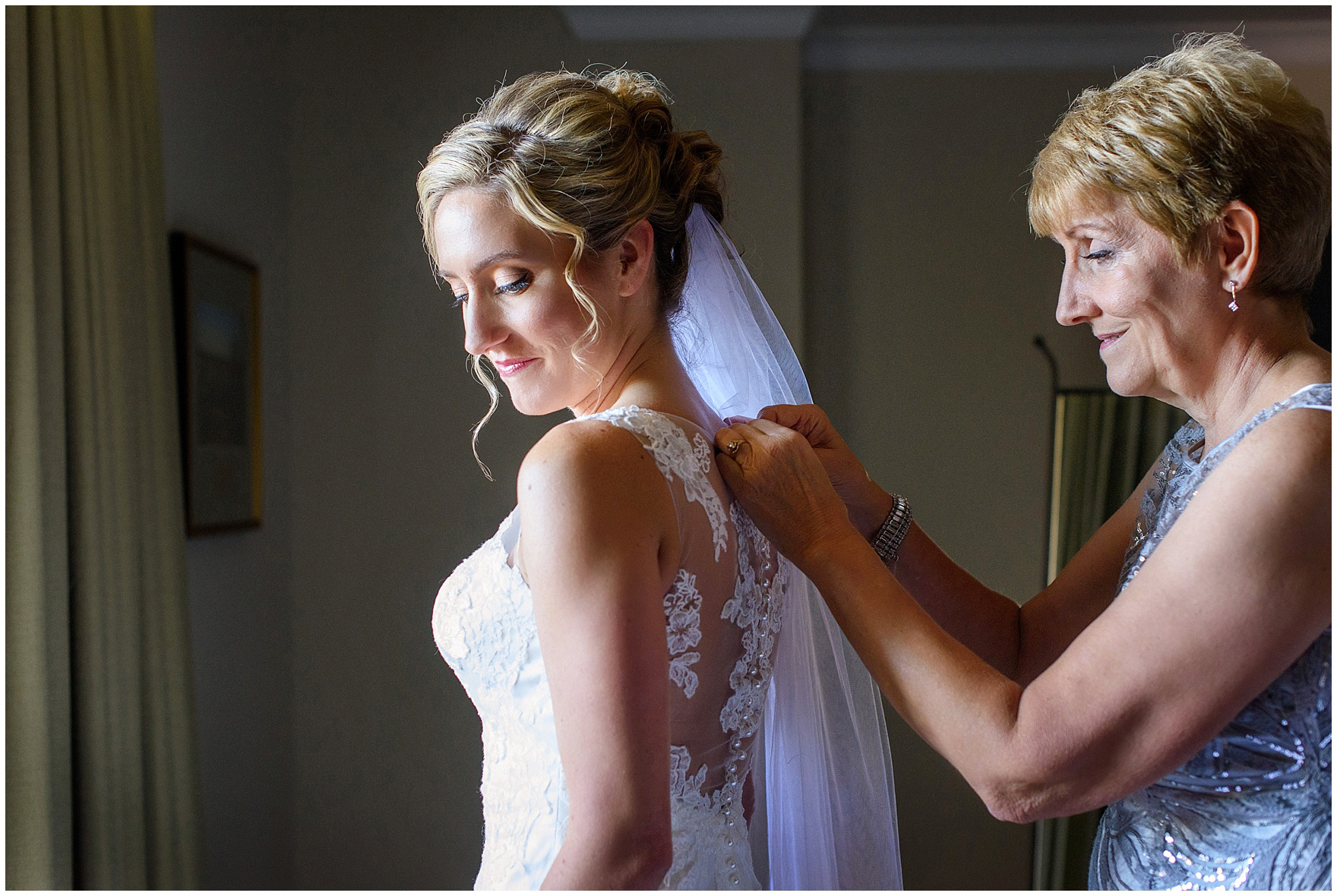 The bride's mother helps fasten her wedding dress before a Glen Club Glenview Illinois wedding.