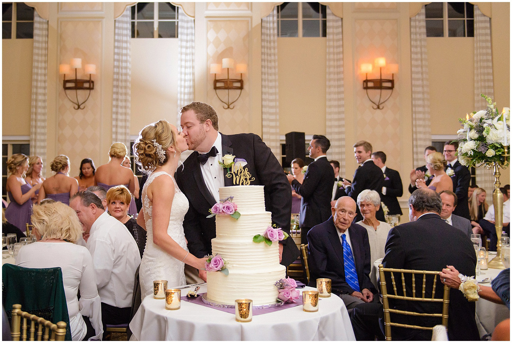 The bride and groom kiss after cutting their cake at a Glen Club Glenview Illinois wedding.