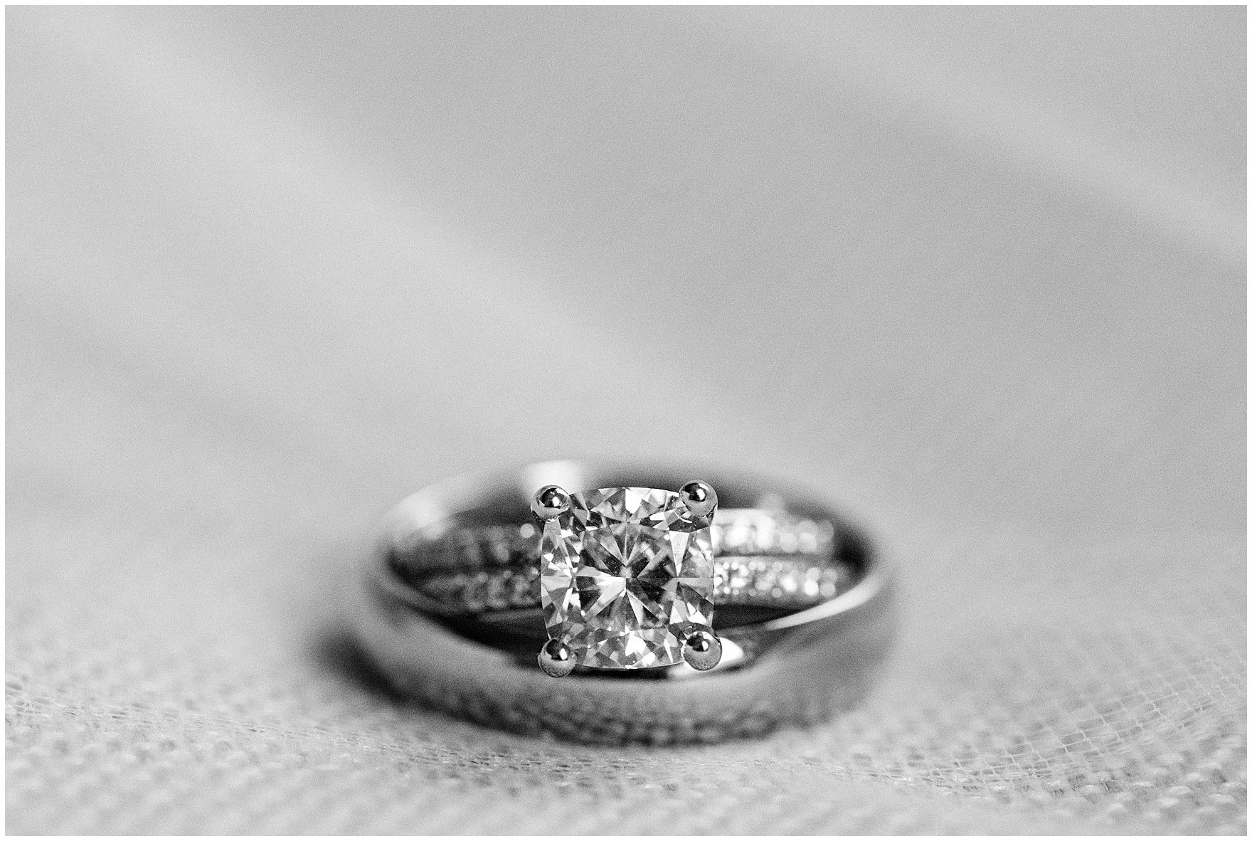 Black and white photograph of a diamond engagement ring and wedding bands at the Ambassador Hotel before a St. Clement Germania Place Chicago wedding.