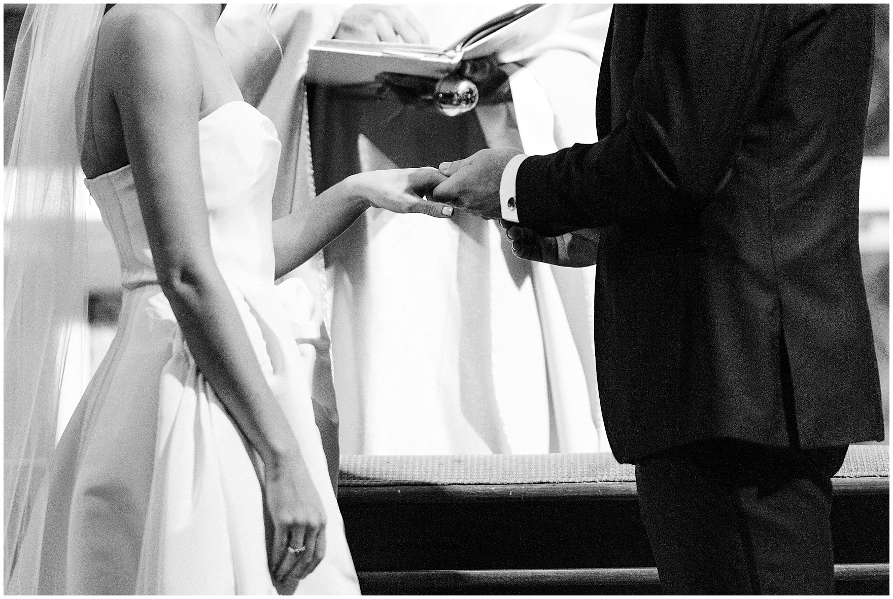 The groom places a ring on the bride's hand during a St. Clement Germania Place Chicago wedding.