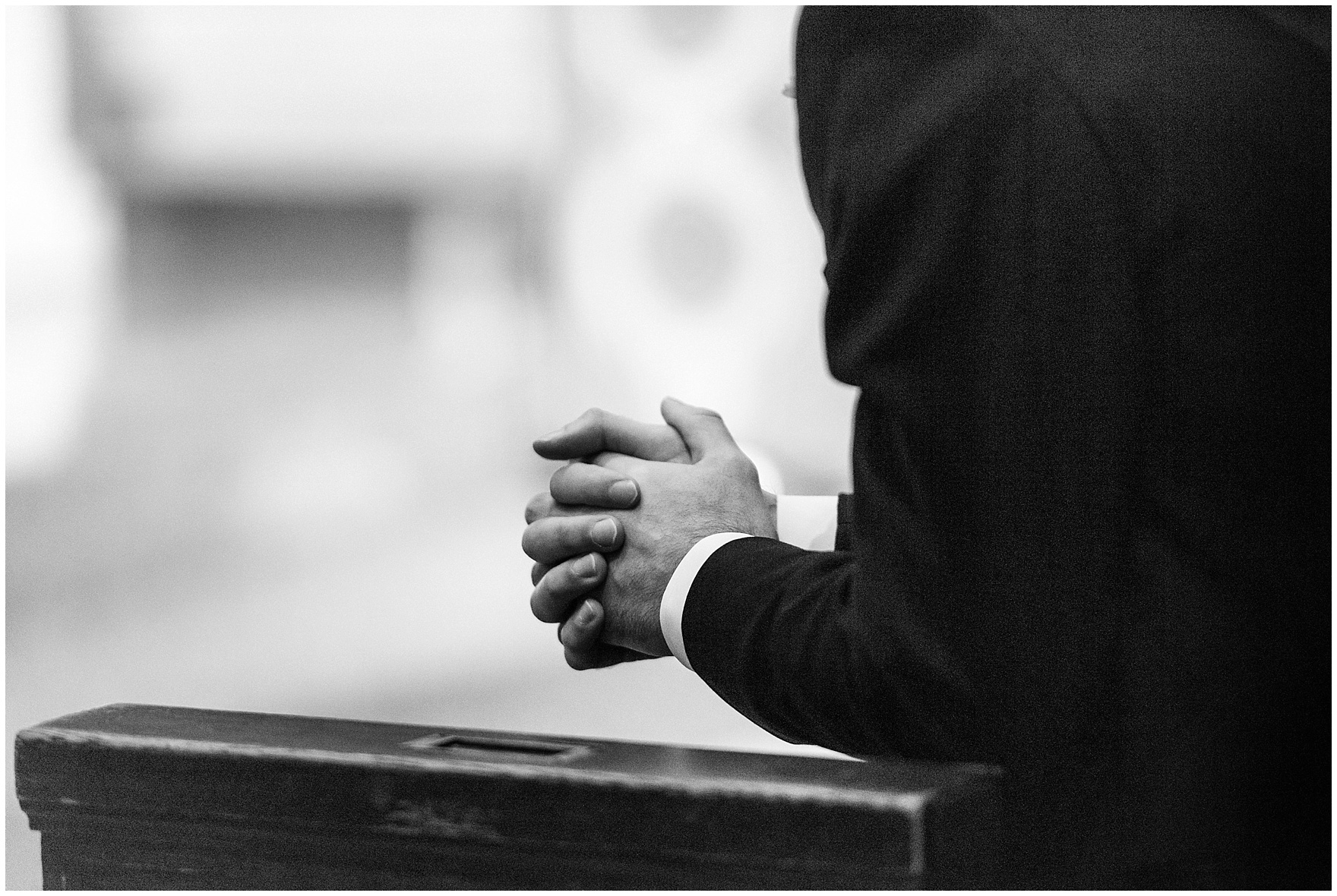 A groomsman's hands are clasped in prayer during a St. Clement Germania Place Chicago wedding.