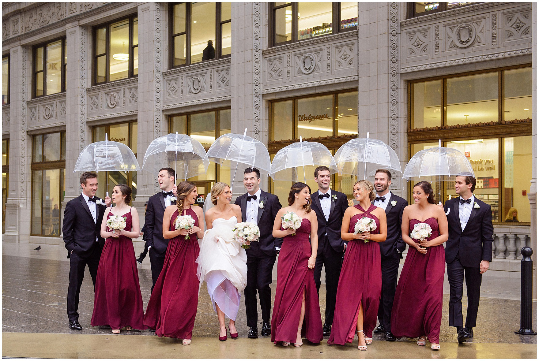 The bridal party carries umbrellas as they walk in front of the Wrigley Building during a St. Clement Germania Place Chicago wedding.