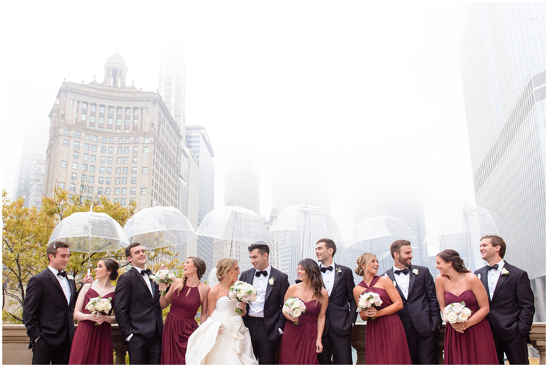 A bride and groom and their bridal party pose along the Chicago river holding umbrellas on a rainy day during a St. Clement Germania Place Chicago wedding.