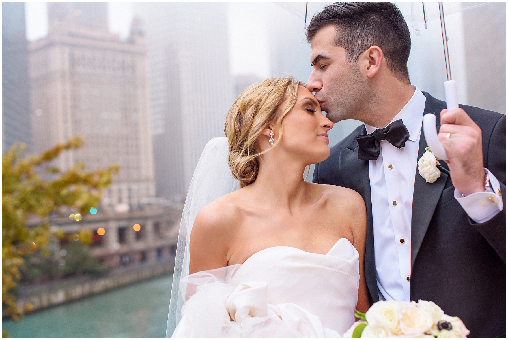 A groom kisses his bride under an umbrella in downtown Chicago during a St. Clement Germania Place Chicago wedding.