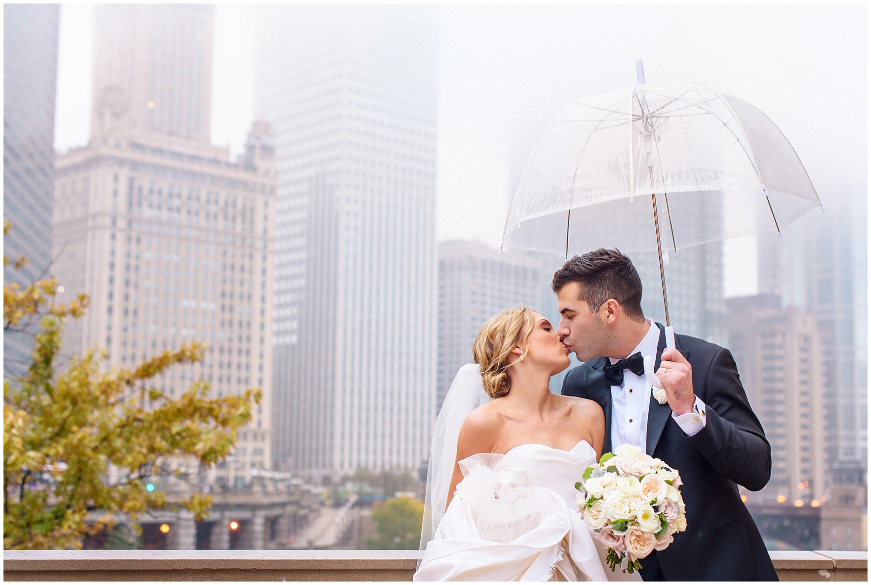 A bride and groom kiss in downtown Chicago on a rainy wedding day during a St. Clement Germania Place Chicago wedding.