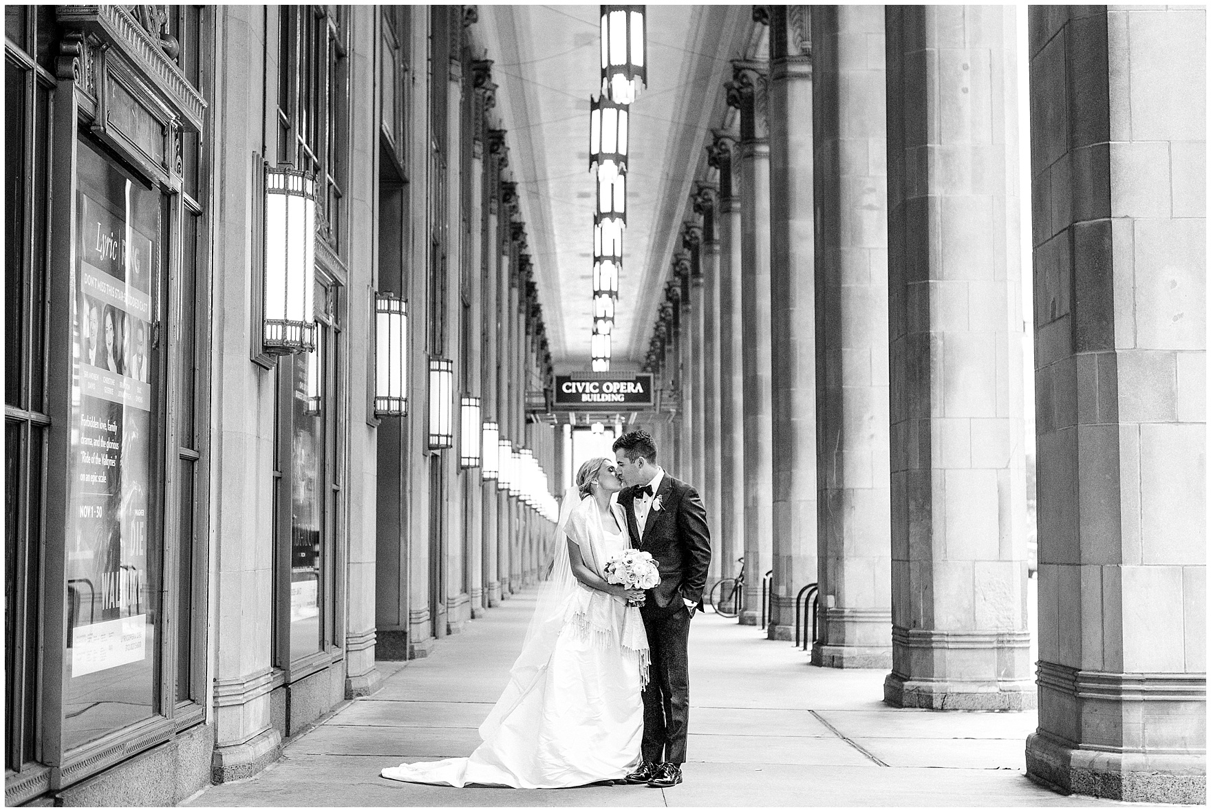 A black and white portrait of the bride and groom between the Civic Opera House columns during a St. Clement Germania Place Chicago wedding.