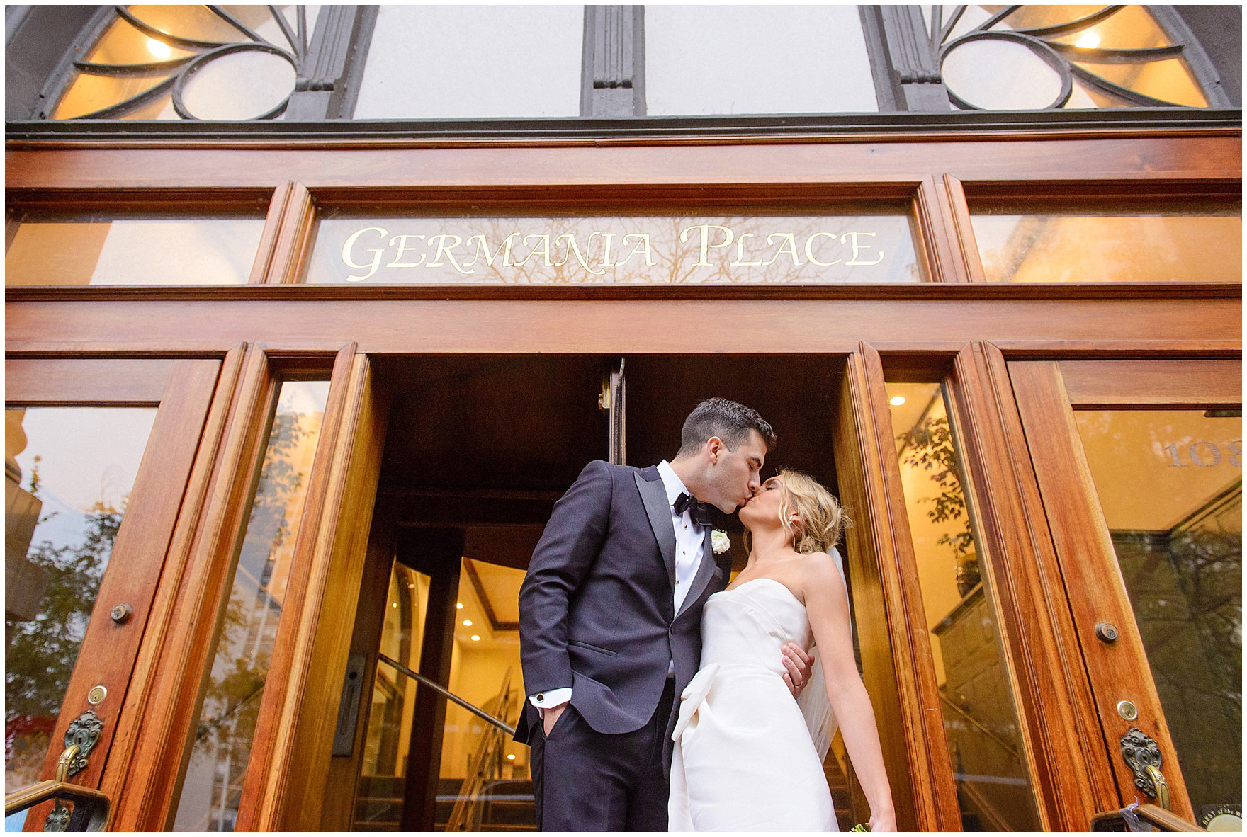 A bride and groom kiss at the entrance to their reception during a St. Clement Germania Place Chicago wedding.