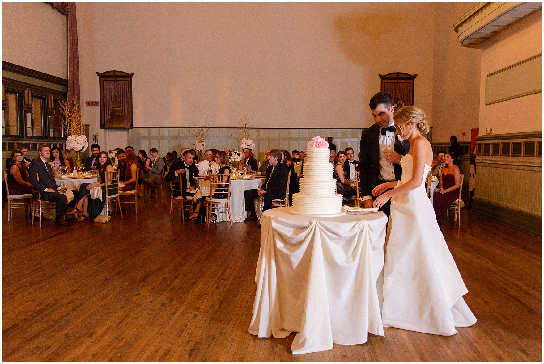 The bride and groom cut their cake during a St. Clement Germania Place Chicago wedding.
