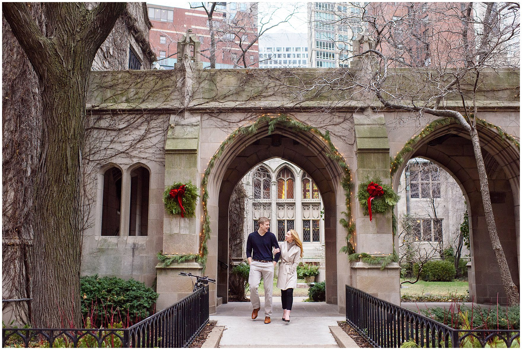 A couple stands beneath the arches of Fourth Presbyterian Church during a downtown Chicago classic engagement photography session.