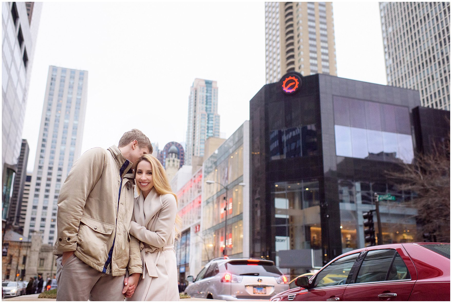 A couple stands among the bustle of Michigan Avenue during a downtown Chicago classic engagement photography session.