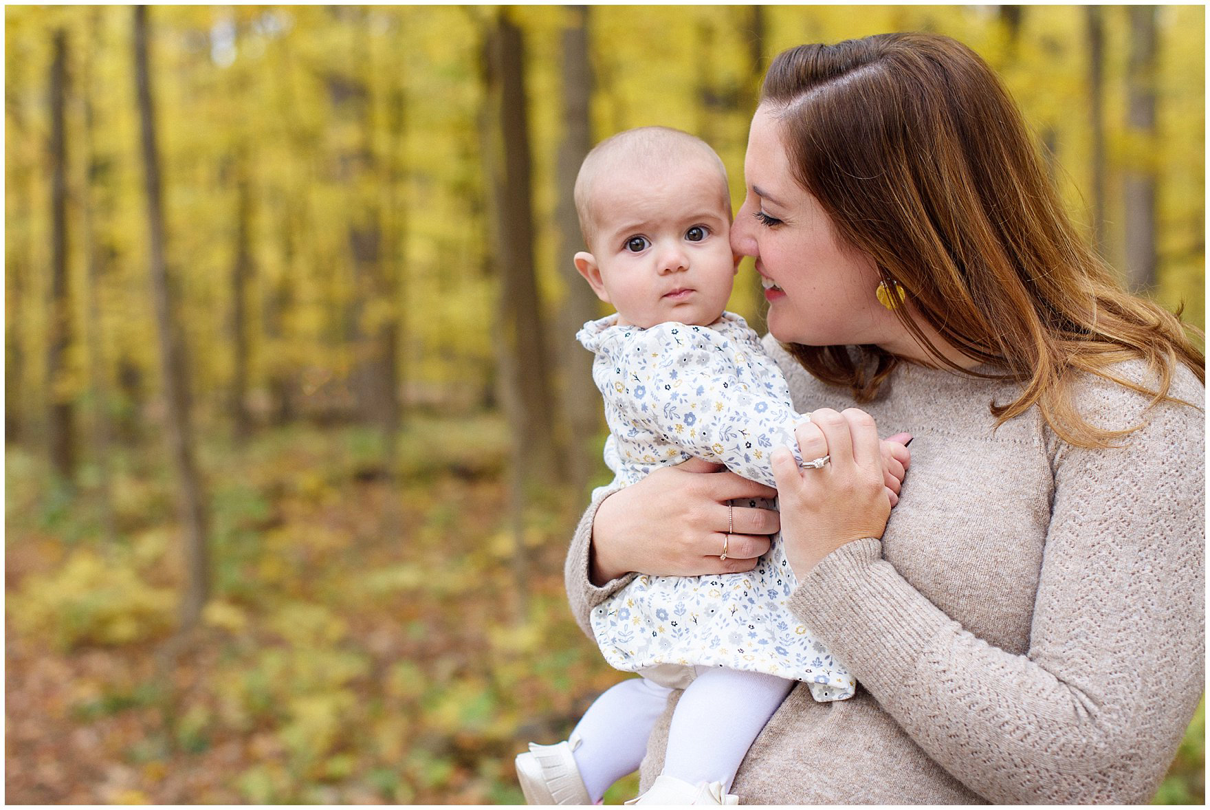 A mom snuggles her baby girl against a backdrop of golden leaves during a Morton Arboretum fall family session.