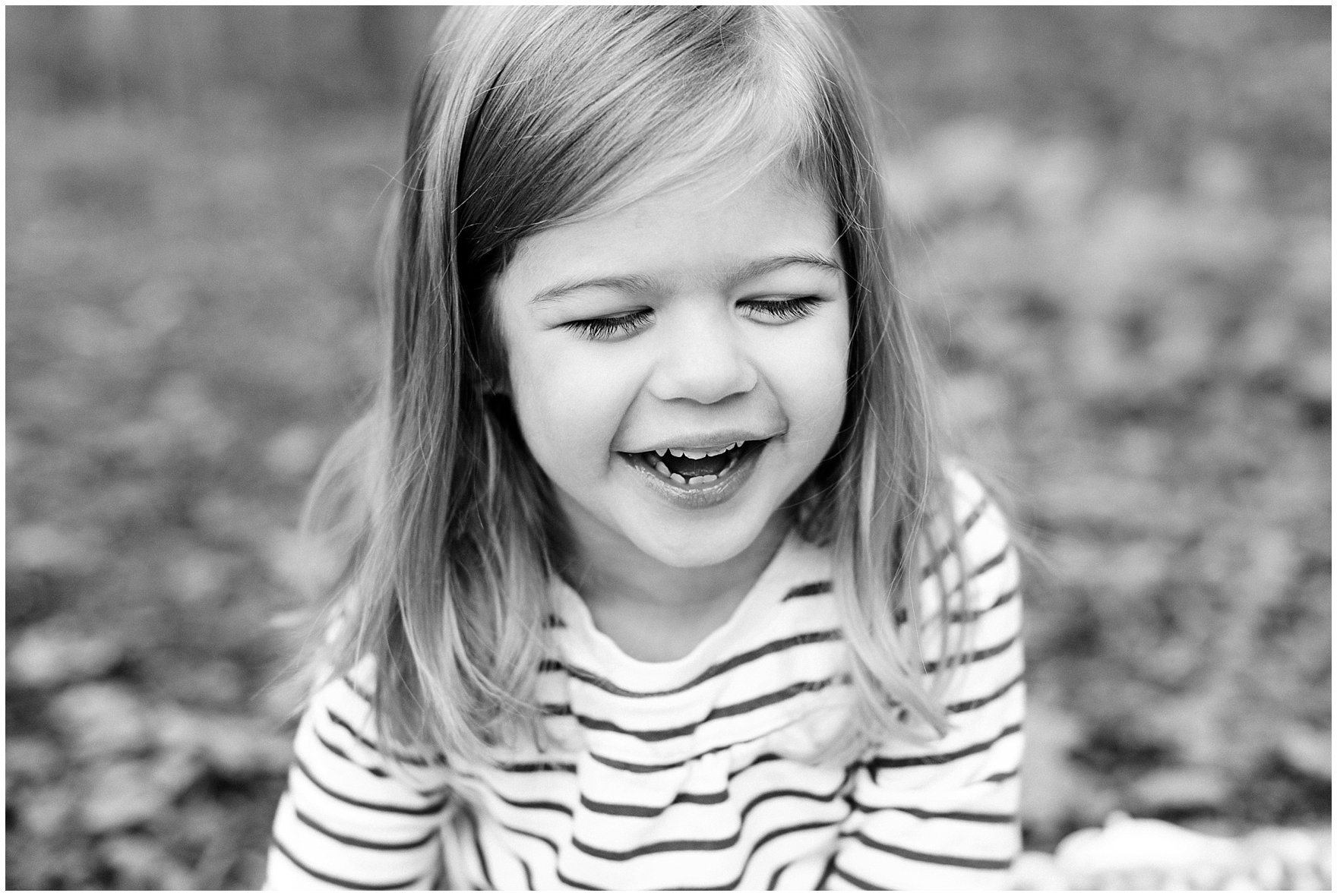 A young girl laughs during a Morton Arboretum fall family session.