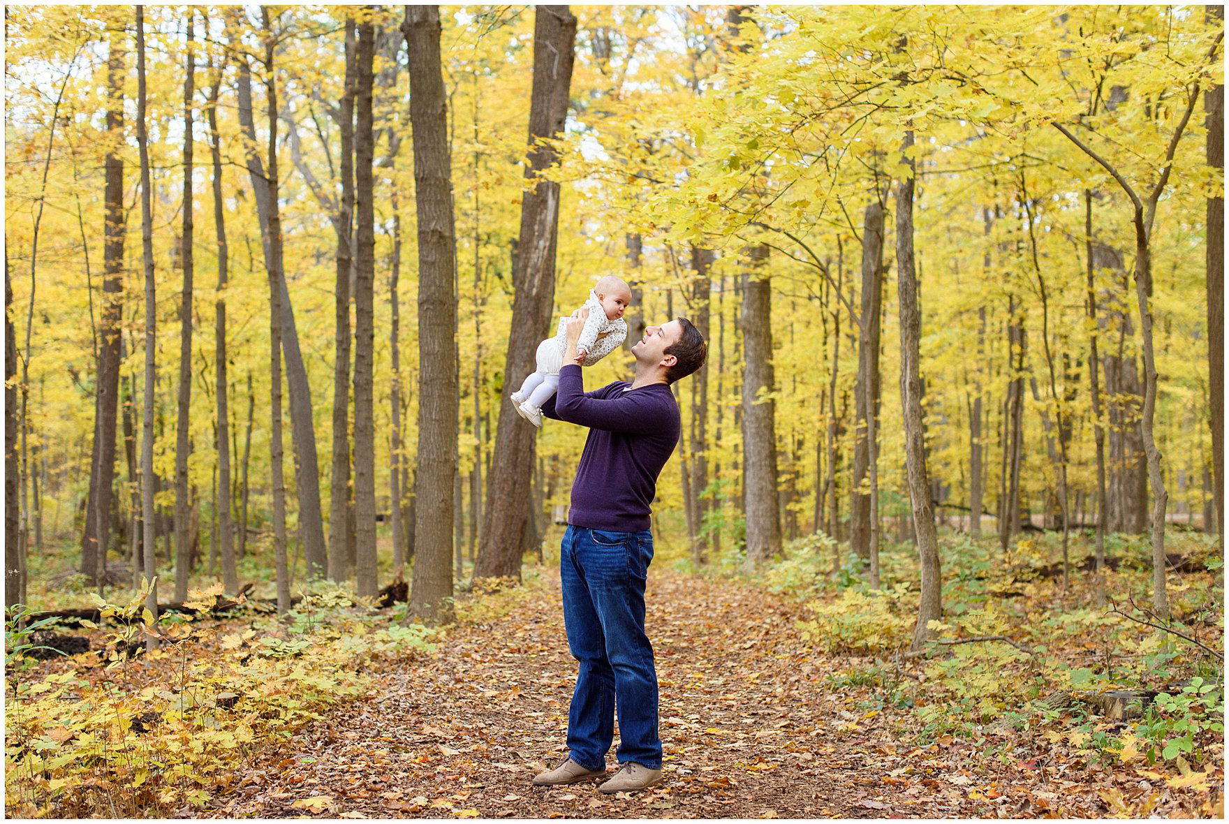 A dad plays with his baby daughter against a backdrop of golden leaves during a Morton Arboretum fall family session.