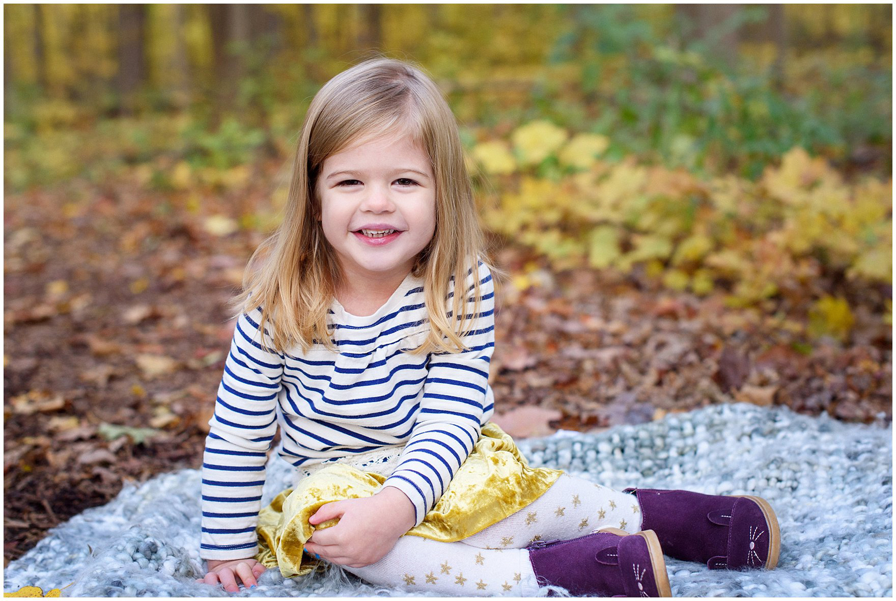 A toddler girl poses on a blanket in front of a backdrop of golden leaves during a Morton Arboretum fall family session.