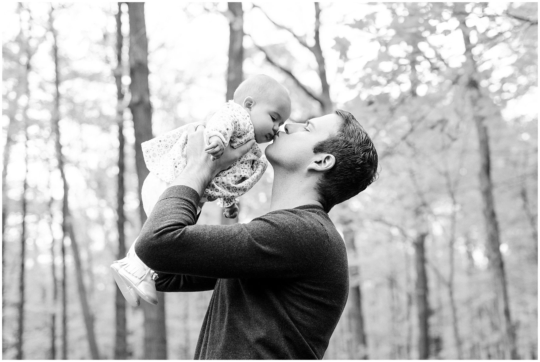 Dad kisses his baby daughter during a Morton Arboretum fall family session.