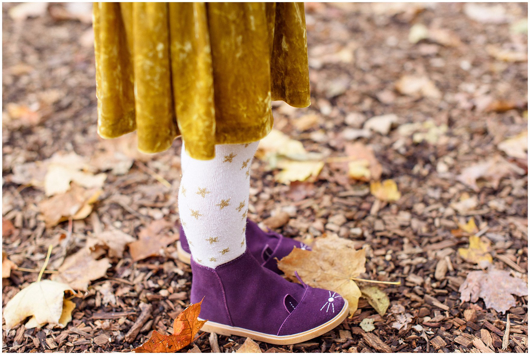 Close up of a girls purple boots and tights with stars during a Morton Arboretum fall family session.