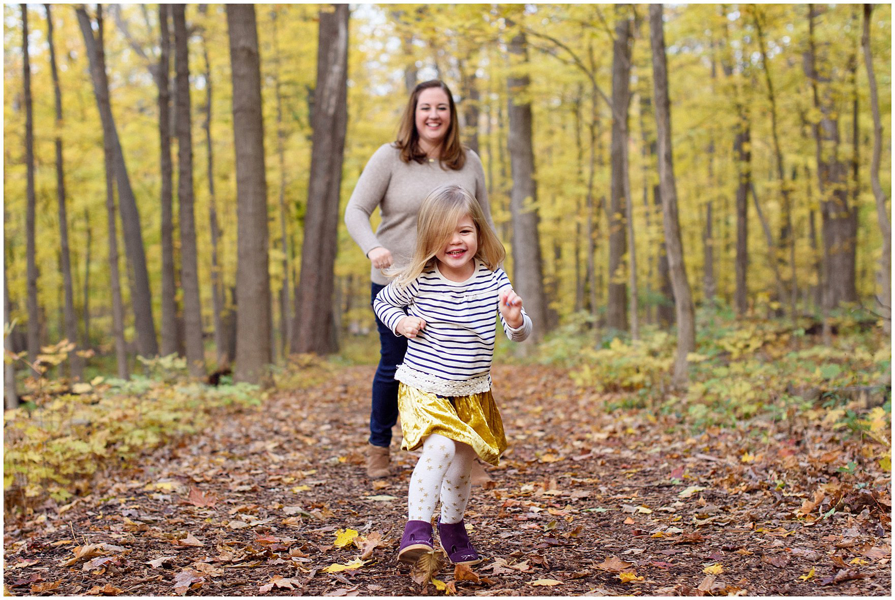 A young girl runs through a forest of golden leaves during a Morton Arboretum fall family session.