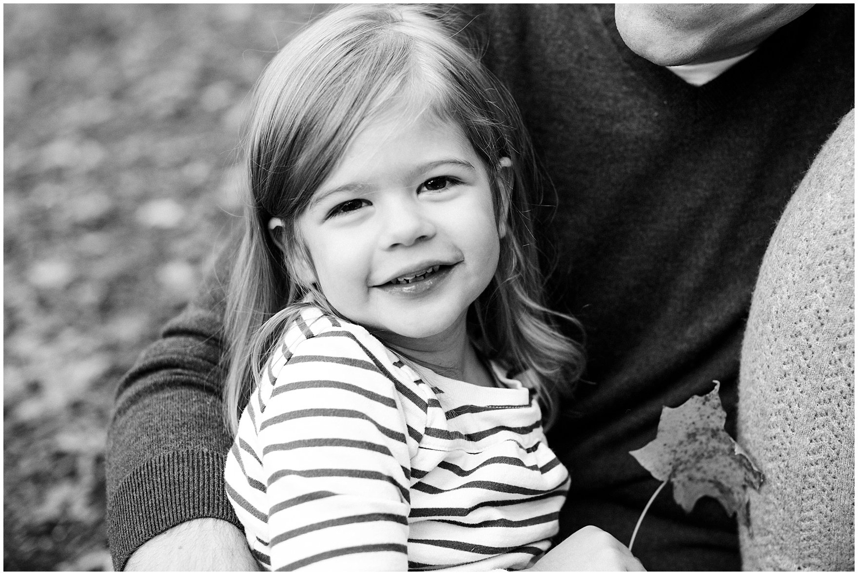 A little girl holds a leaf and snuggles with her dad during a Morton Arboretum fall family session.
