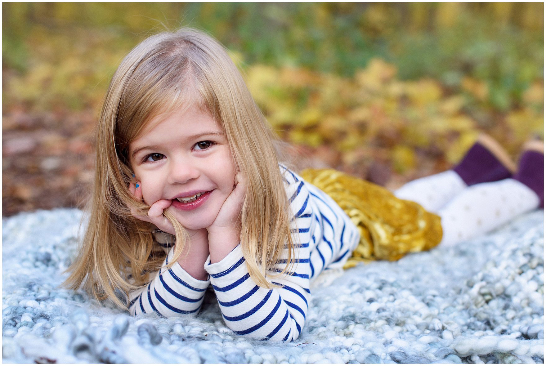 A young girl lays on a blanket in front of a backdrop of golden leaves during a Morton Arboretum fall family session.