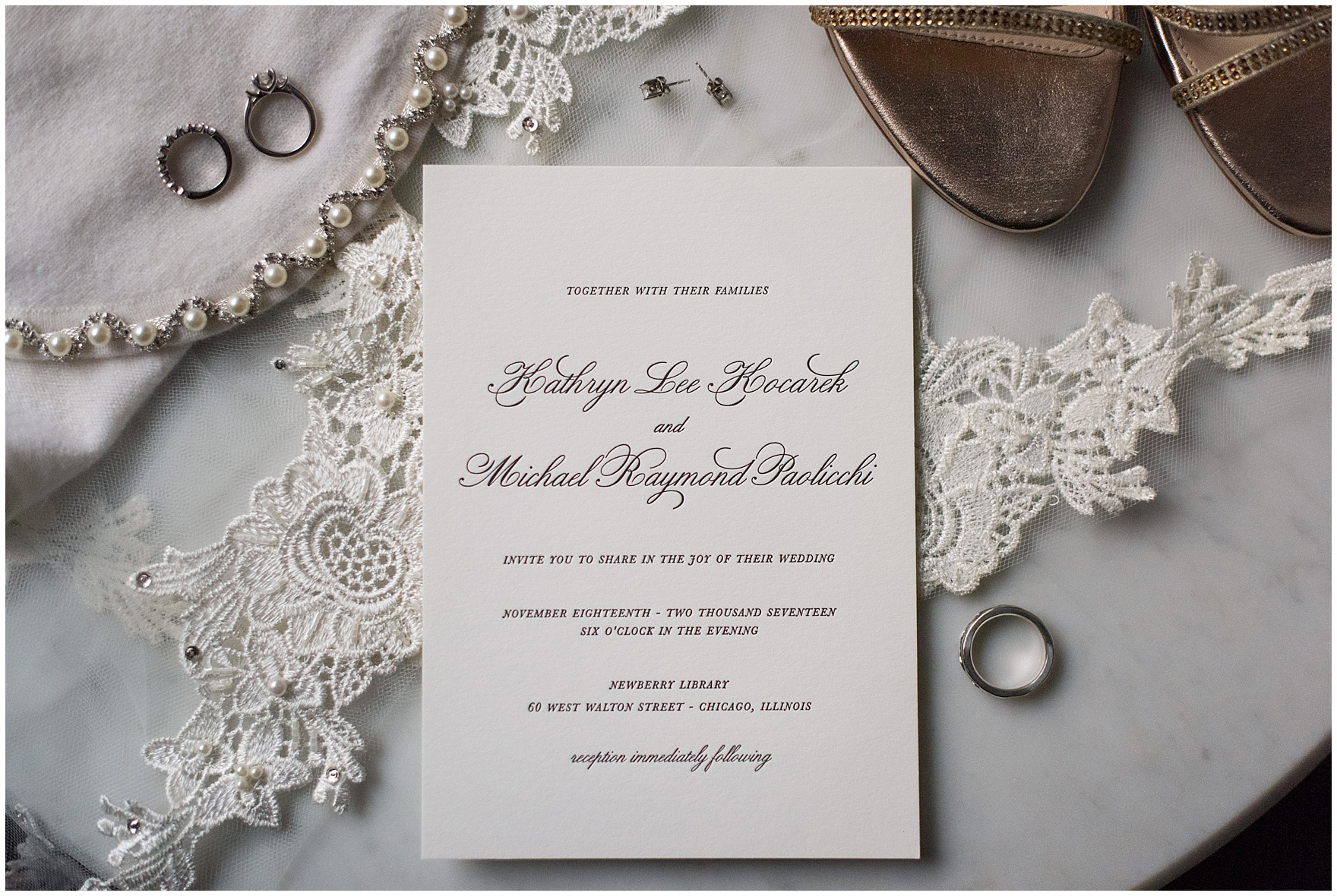 Details of a letterpresse wedding invitation with wedding rings, shoes, and veil for a Newberry Library Chicago wedding.