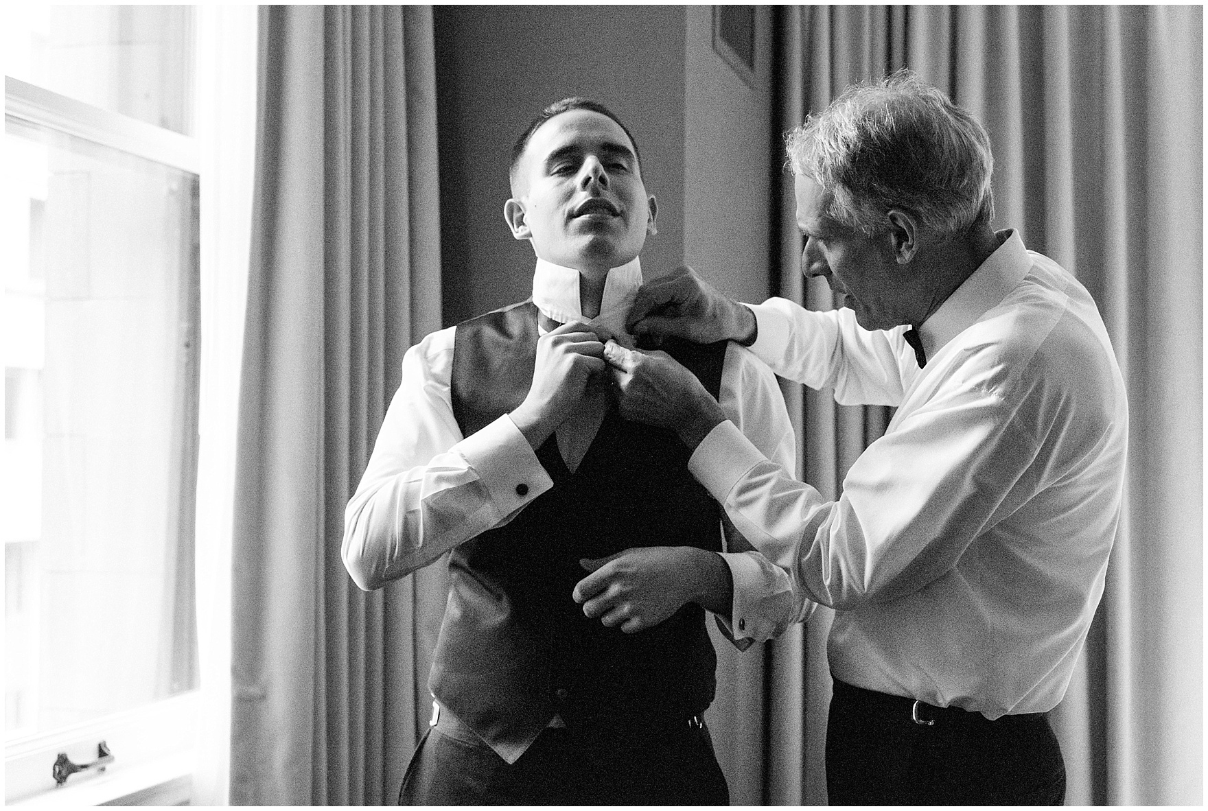 The groom's father helps with his tie for a Newberry Library Chicago wedding.