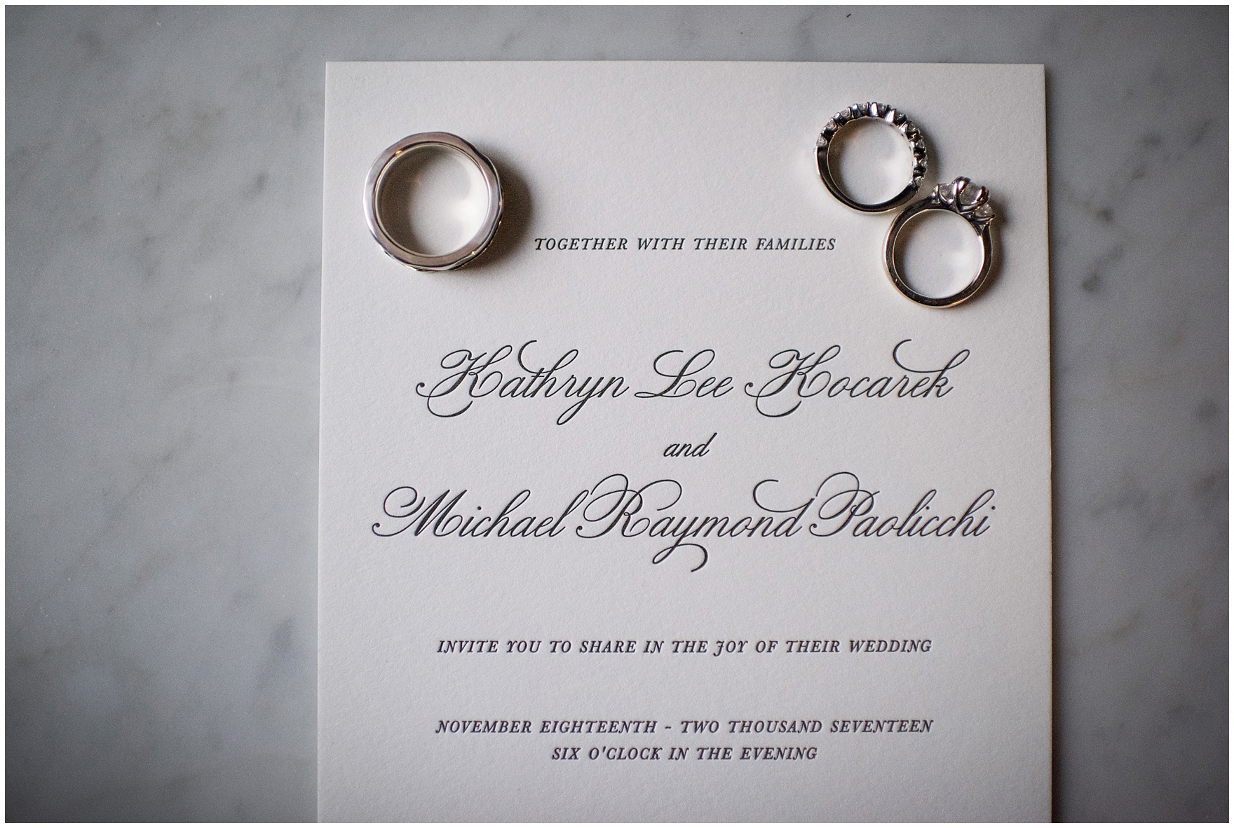 The wedding bands and engagement ring are photographed on a letterpress wedding invitation for a Newberry Library Chicago wedding.