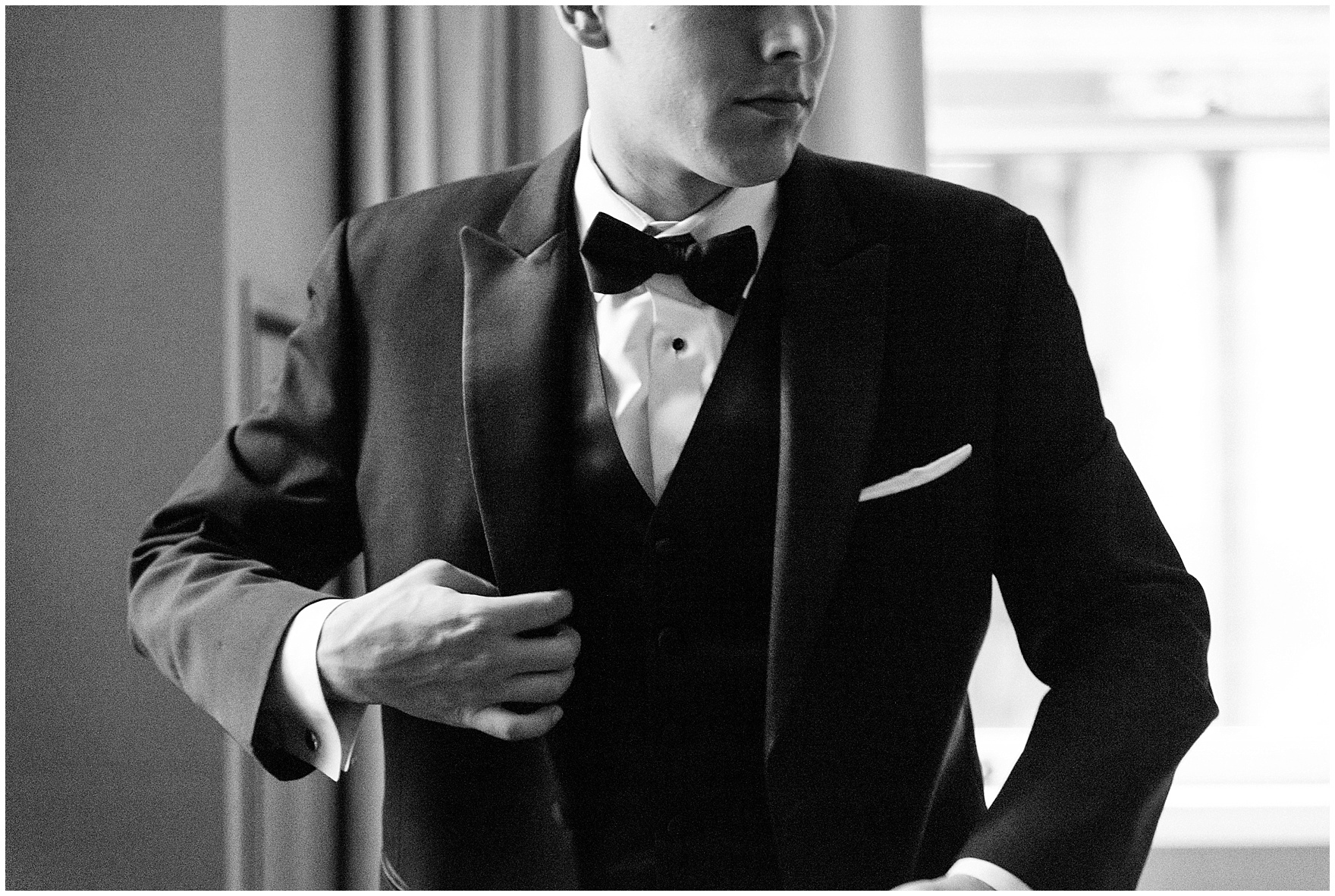 The groom puts on his jacket at the Gray Hotel Chicago for a Newberry Library Chicago wedding.